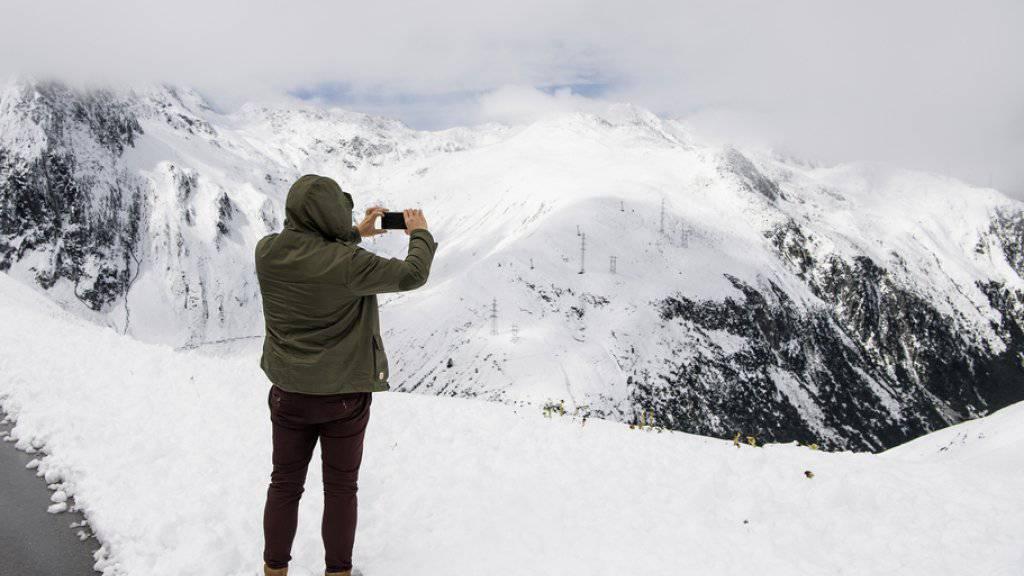Ein Tourist macht am 10. September auf der Nufenenpassstrasse ein Foto der eingeschneiten Berglandschaft.