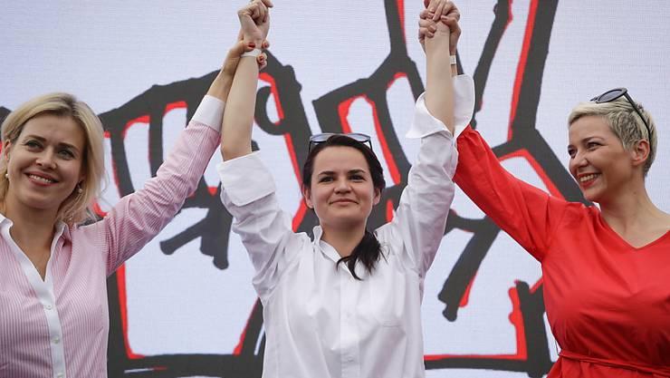 Maria Kolesnikowa, Swetlana Tichanowskaja und Veronika Zepkalo stehen bei einem Wahlkampfauftritt in der belarussischen Hauptstadt Minsk zur Unterstützung von Tichanowskaja. Foto: Sergei Grits/AP/dpa