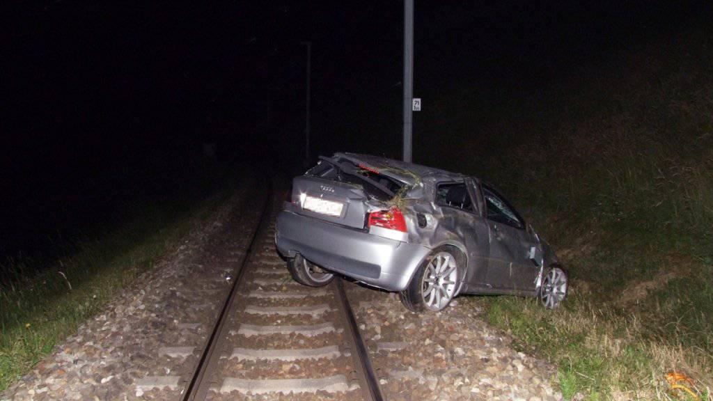 Auf den Zuggleisen gelandet: Aus dem beschädigten Unfallauto konnte sich der Lenker leicht verletzt befreien.
