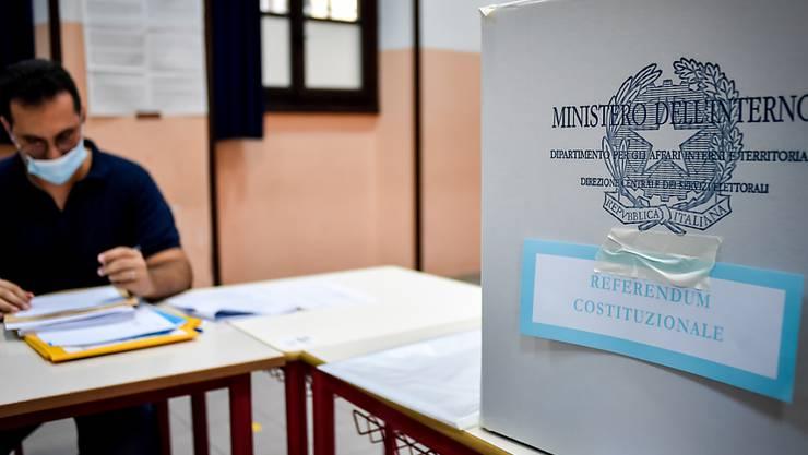 Ein Wahlhelfer sitzt an einem Tisch neben in der Parini-Mittelschule neben einer Wahlurne. Foto: Claudio Furlan/LaPresse via ZUMA Press/dpa