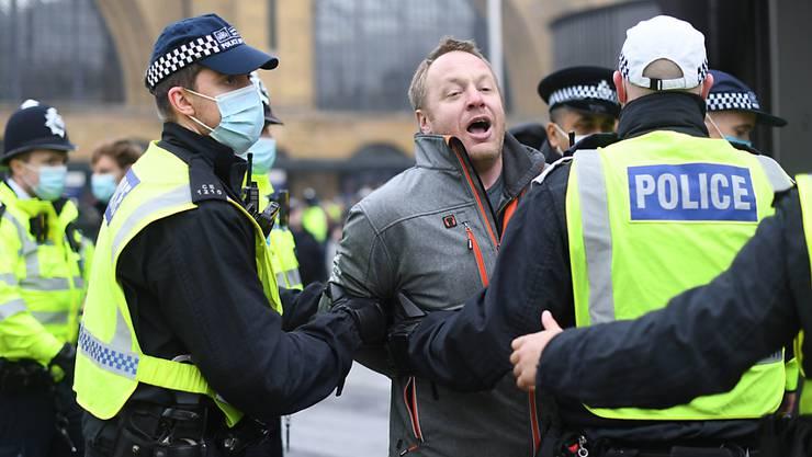 Ein Mann wird während einer Demonstration von Polizisten weggeführt. Foto: Stefan Rousseau/PA Wire/dpa