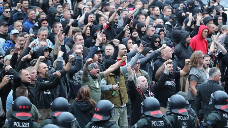 Polizisten stehen in der Innenstadt am Karl-Marx-Monument bei einer Kundgebung der rechten Szene, um ein Aufeinanderprallen von rechten und linken Gruppen zu verhindern. Nach einem Streit war in der Nacht zu Sonntag in der Innenstadt ein 35-jähriger Mann erstochen worden. Die Tat war Anlass für spontane Demonstrationen, bei denen es auch zu Jagdszenen und Gewaltausbruechen kam.