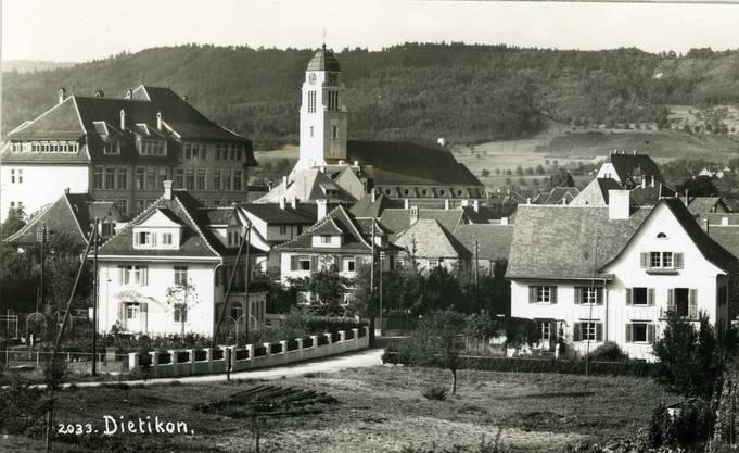 Diese Dorfansicht von Dietikon stammt aus dem Jahr 1930. Im Vordergrund links ist das heutige Ortsmuseum, die ehemalige Villa Strohmeier an der Schöneggstrasse 20, zu erkennen. Sie wurde 1927 vom Bankier Walter Strohmeier erstellt. Die Familie galt als die reichste im Dorf. Zum Anwesen gehörten ein grosser Garten und ab 1947 auch ein Tennisplatz. 1968 wurde die Villa von der Stadt erworben. Seit 1978 befindet sich das Ortsmuseum darin. Dieses war zuvor während 20 Jahren im Brenn-, Schwenk- oder auch Färberhüsli genannten Häuschen an der oberen Reppischstrasse 16 beheimatet.