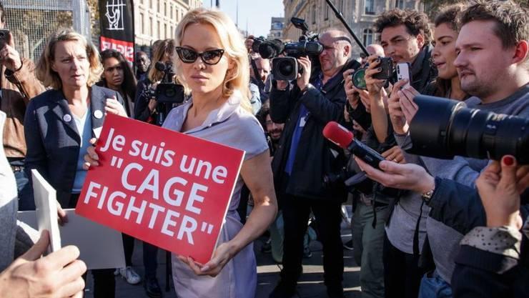 Pamela Anderson (Mitte) hat sich in einen Käfig einsperren lassen. Damit protestierte sie gegen die Haltung von Zuchttieren.