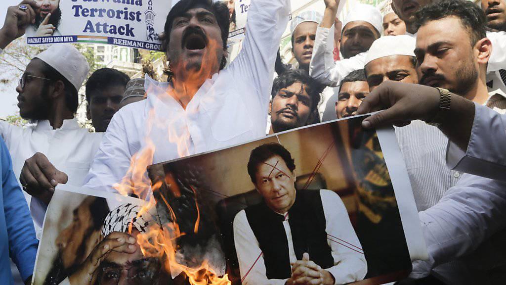 Indische Muslime wegen des Anschlags auf den paramilitärischen Konvoi in Kaschmir, der mindestens 40 Menschen getötet hatte. Sie verbrennen Plakate des pakistanischen Premierministers Imran Khan (Mitte).