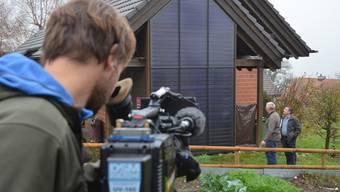 Kameramann Iwan Aeschbacher filmt Gemeindeammann Daniel Appert und Fernsehjournalist Reto Holzgang bei Besichtigungen im Dorf.
