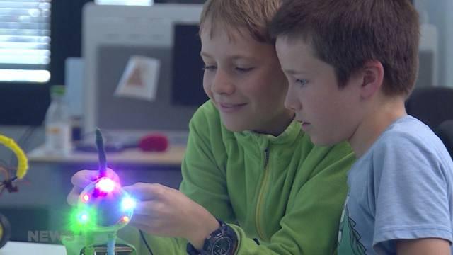 Kinder bauen und programmieren tanzende Roboter