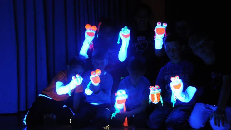 Die selbst gebastelten Handpuppen lassen die Kinder im Schwarzlicht tanzen.