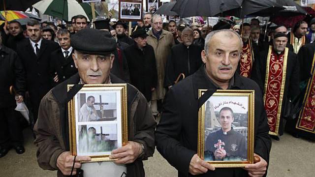 Kundgebungsteilnehmer halten Bilder von christlichen Opfern in den Händen
