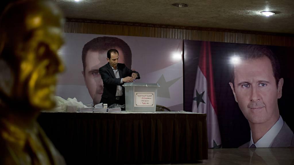 ARCHIV - Ein Wahlhelfer steht in einem Wahllokal mit Plakaten von Präsident Baschar al-Assad .  Die Führung des Bürgerkriegslandes Syrien plant Ende kommenden Monats eine Präsidentschaftswahl. Foto: Hassan Ammar/AP/dpa