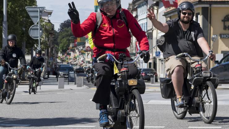 Gute Laune mit 30 km/h: Teilnehmer der Umrundung des Genfersees mit ihren Lieblingsuntersätzen bei der Ortsdurchfahrt in Rolle.