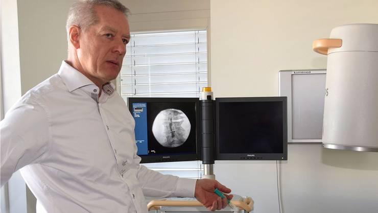 Arzt Urs Hintermann behandelt die Schmerzpatienten im medizinischen Zentrum mit einem brandneuen, leistungsstarken Gerät.