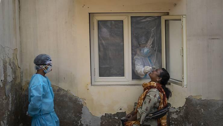 dpatopbilder - Ein mit einem Schutzanzug bekleideter Mitarbeiter des Gesundheitswesens nimmt bei einer Frau in einem Covid-19-Testzentrum im indischen Neu Delhi eine Nasenabstrichprobe. Foto: Altaf Qadri/AP/dpa