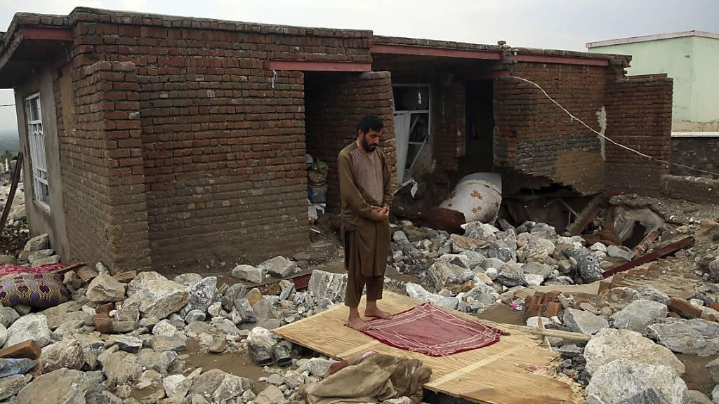 Ein Mann betet neben seinem Haus in Parwan, das von einer Schlammlawine zerstört wurde. Landesweit sind bei Sturzfluten dutzende Menschen gestorben. Foto: Rahmat Gul/AP/dpa
