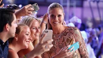 Heidi Klum posiert geduldig mit ihren Fans für Selfies.