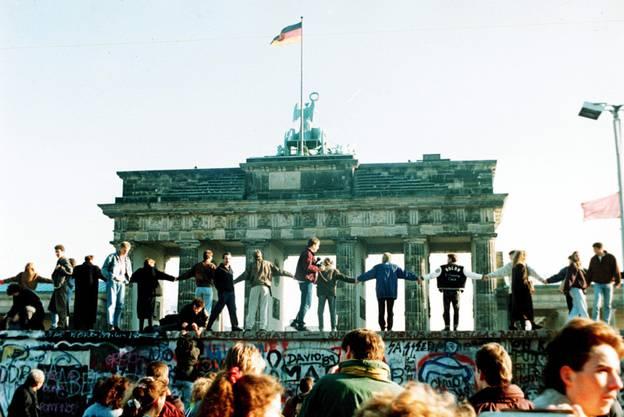 Die ersten Steine sind gefallen: Menschen aus Ost und West tanzen am Tag nach der Grenzöffnung auf der Mauer vor dem Brandenburger Tor in Berlin am 10. Nov. 1989.