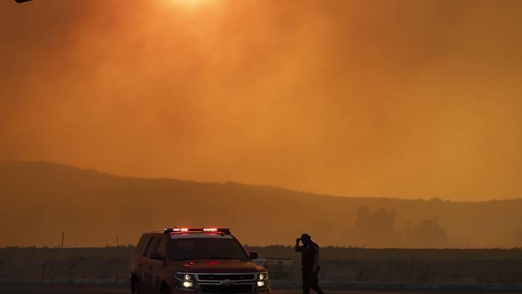 Ein Polizeiauto steht im dichten Rauch eines Waldbrandes. Ein schnell um sich greifendes Feuer hat Einwohner im US-Staat Kalifornien etwa 70 Kilometer südöstlich von Los Angeles aufgeschreckt. Foto: Mindy Schauer/The Orange County Register/AP/dpa
