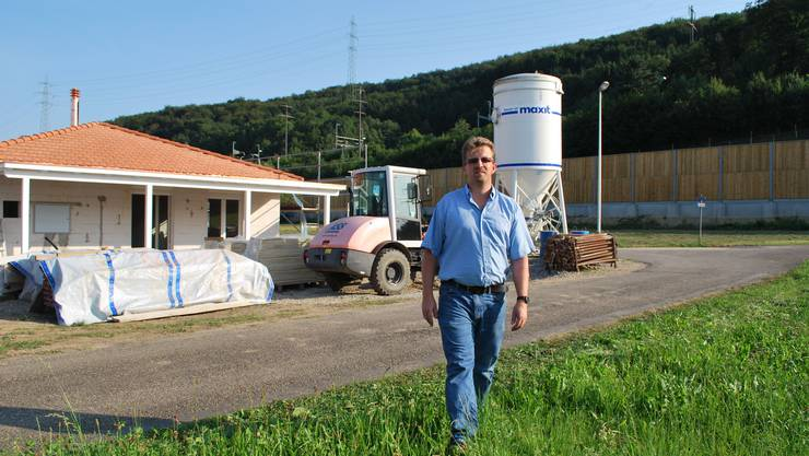 Gemeindeammann Jürg Müller vor einer Baustelle im Gebiet Zelgli in Mumpf. Im Hintergrund ist die neue Lärmschutzmauer erkennbar. lbr