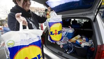 Eine Lidl-Kundin verstaut ihre Einkäufe im Auto.
