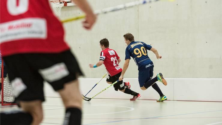 Unihockey: 1.-Liga-Derby Waldenburg Eagles (blau) - Unihockey Basel Regio (rot). Michael Keerli wird von Tobias Bitterli verfolgt.
