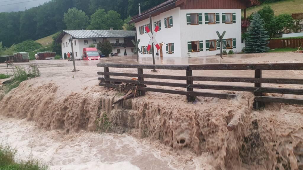 Wasser fließt über einen Platz vor einem Haus. im oberbayerischen Landkreis Berchtesgadener Land. Foto: Kilian Pfeiffer/dpa