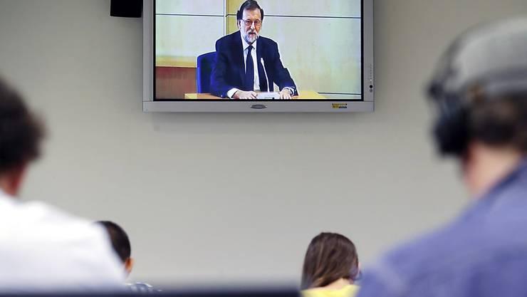 Journalisten verfolgend die Aussage Rajoys über einen Bildschirm.