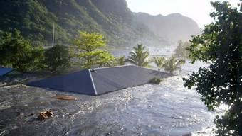 In Apia, der Hauptstadt des pazifischen Inselstaates Samoa, wird im September 2009 ein Hausdach von einer Tsunami-Welle fortgespült (Archiv)