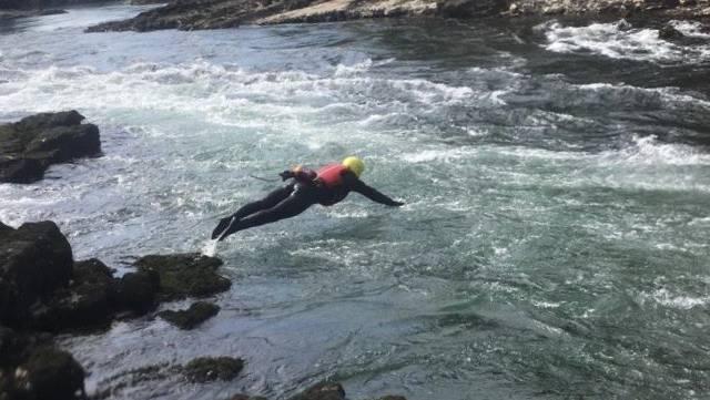 Ein Foto einer Übung. Der Rettungsschwimmer trägt einen Neopren-Anzug, Helm und Schwimmwes-te. Der Kopfsprung ist nur möglich, da er das Gewässer sehr gut kennt. An der Schwimmweste wurde bei der Rettung ein Seil befestigt, um den Schwimmer mit der geretteten Person sicher an Land zu bringen.