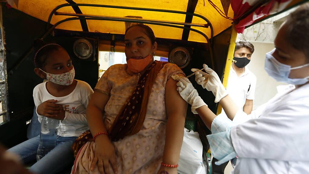 Eine Mitarbeiterin des Gesundheitswesens impft in Ahmedabad eine Frau gegen das Coronavirus.