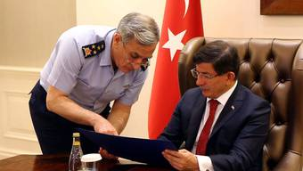 Der Chef der türkischen Luftwaffe Akin Ozturk (L) im Gespräch mit Regierungschef Ahmet Davutoglu (R). Die Regierung bestätigte am Montag die Luftangriffe gegen PKK-Stellungen.