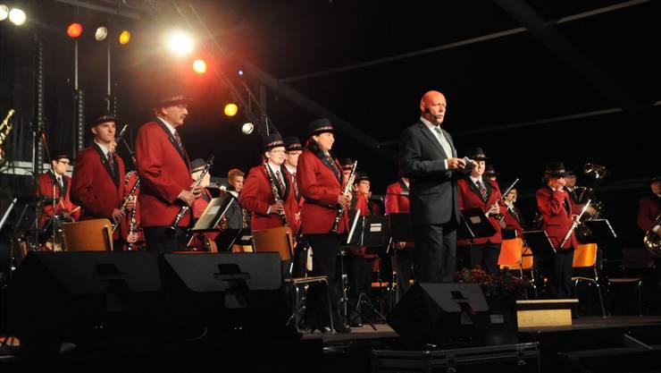 Die Musiker in ihren neuen Uniformen und Moderator Hans Peter Bachmann am Konzert des Gala-Dinners.