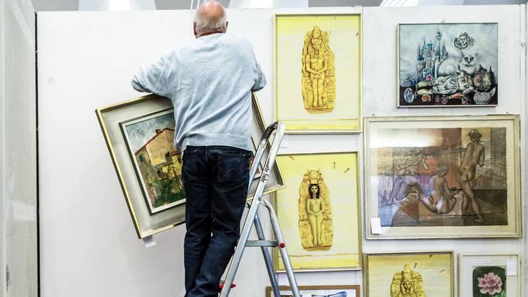 Der freiwillige Helfer Urs Rohr hängt die Bilder auf: «Ich bin kein Kunstkenner. Für mich ist das Wichtigste, dass die Bilder gerade hängen», sagt er lachend.