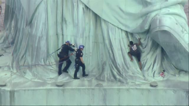 Frau klettert auf Freiheitsstatue