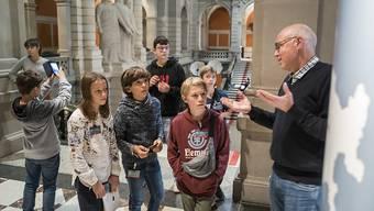 Andreas Blaser, Leiter Öffentlichkeitsarbeit der Parlamentsdienste (rechts), führt Kinder, die am Keystone-SDA-Zukunftstag teilnehmen, durch das Bundeshaus.