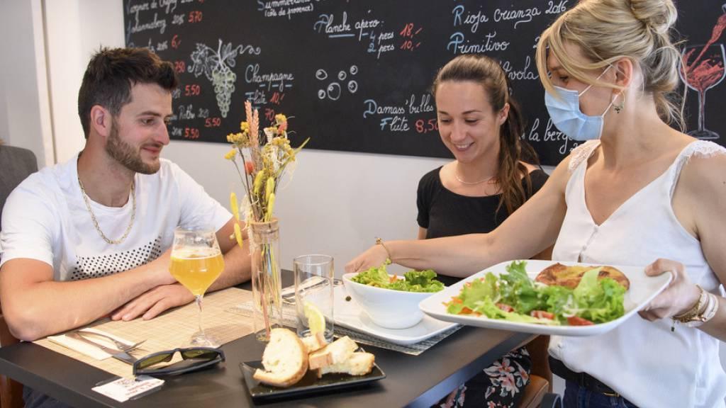 In Porrentruy JU freuen sich die ersten Gäste auf ein Mittagessen im Innern eines Restaurants.