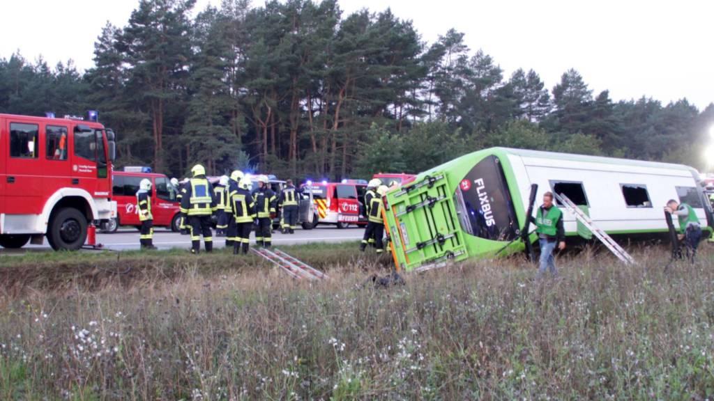 Feuerwehrleute stehen an der Autobahn A24 neben einem verunglückten Fernbus. Bei dem Fernbusunglück hat es am frühen Morgen nach Polizeiangaben 31 Verletzte gegeben. Das Unternehmen Flixbus bestätigte der Deutschen Presse-Agentur zunächst 3 Verletzte. Foto: Ralf Drefin/dpa