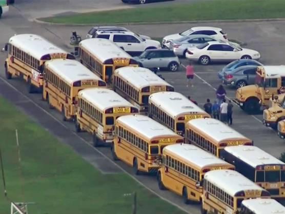 Schulbusse und wartende Personen vor der Santa Fe High School in Texas.