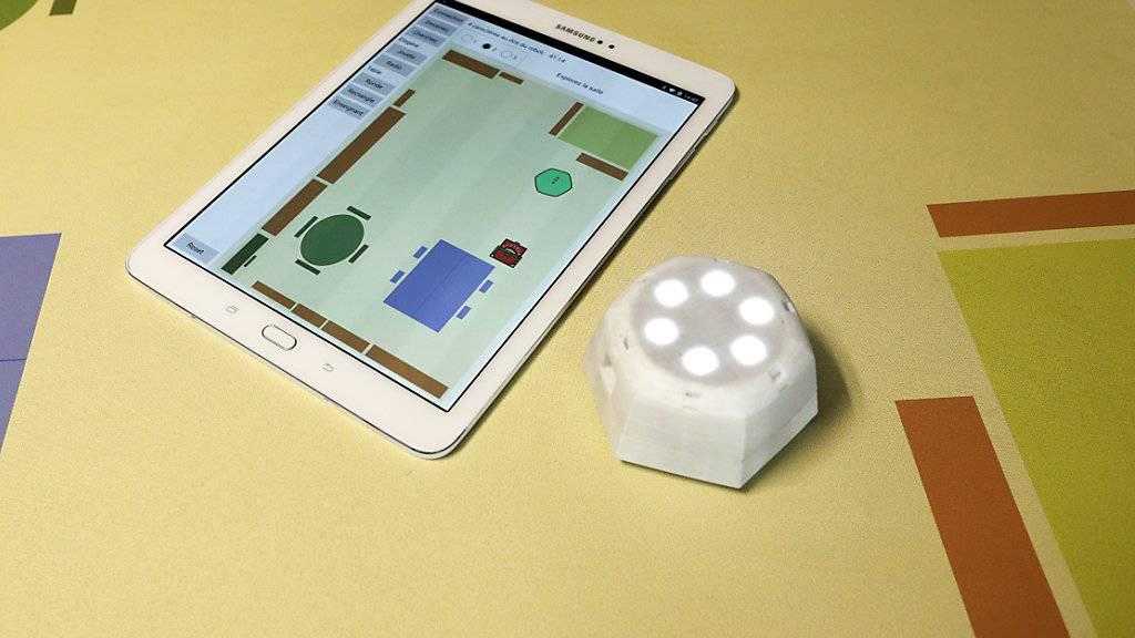 Der handliche Roboter Cellulo wird über die Karte des Klassenzimmer geschoben und reagiert auf die markierten Hindernisse. Seine Position erscheint auch in der dazugehörigen Tablet-Anwendung.