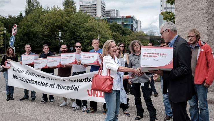 Novartis-Angestellte und die Unia protestieren gegen den geplanten Stellenabbau.