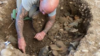 Die mit Keramikfragmenten gefüllte Grube wird sorgfältig ausgegraben.