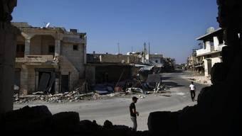 Blick durch eine kaputte Hauswand auf einen Vorort Aleppos (Archiv)