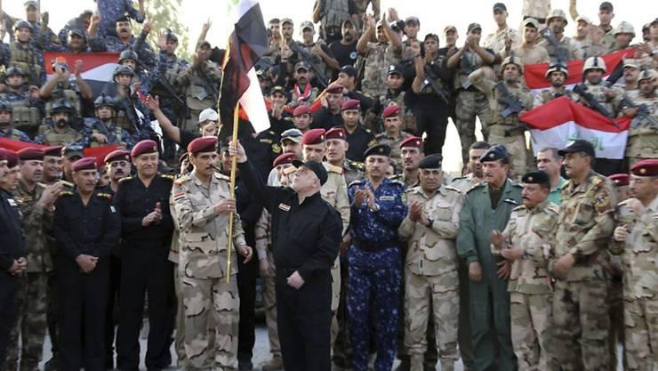 Nach monatelangen Kämpfen hat Iraks Regierungschef Haidar al-Abadi (in schwarzer Kleidung, Bildmitte) die bisherige IS-Hochburg Mossul offiziell für befreit erklärt.