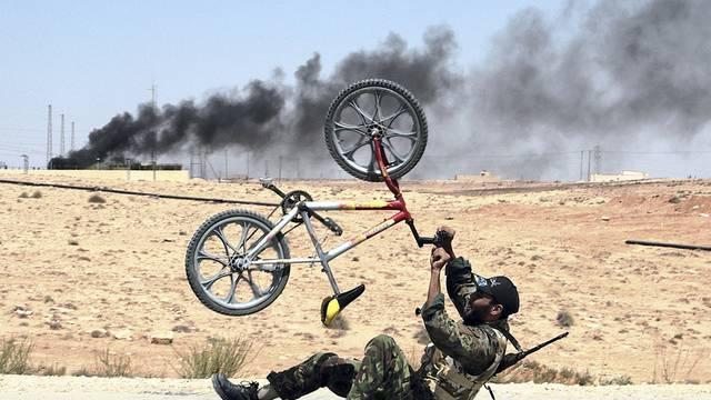 Ein libyscher Rebell mit einem Mountainbike vor der umkämpften Ortschaft al-Kawalisch