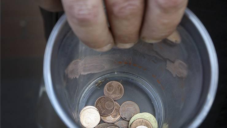 Ein Bettler hält in Düsseldorf einen Becher mit Kleingeld. (Symbolbild)