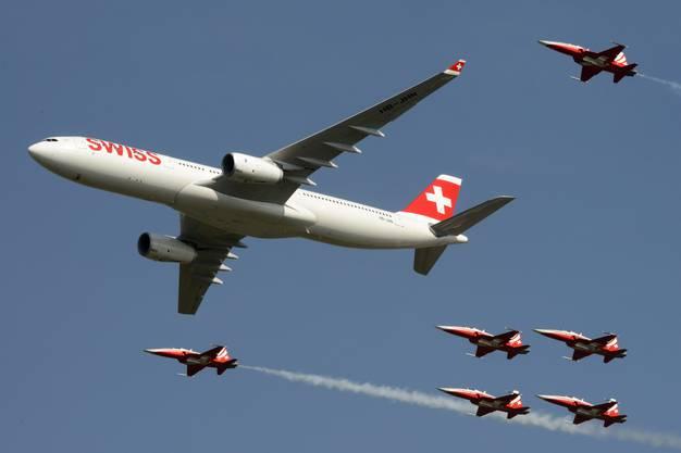 Ein Airbus A330 der Swiss, eskortiert von sechs Tiger-Jets der Patrouille Suisse, überliegt das Gelände.