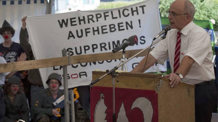 Bundespräsident Ueli Maurer in Biel. Im Hintergrund GSoA-Demonstranten.