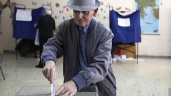 Ein älterer Mann wirft in Athen seinen Stimmzettel ein