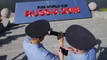 Russische Polizisten vertreiben sich mit ihren Handys die Zeit bei einem Einsatz in St. Petersburg. Nun werden sie von Schweizern unterstützt.REUTERS/Maxim Shemetov