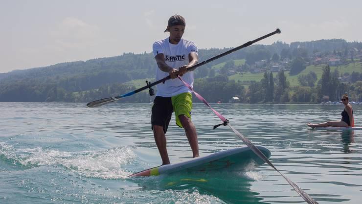 Manu Simmons steht auf einem Surfbrett und lässt sich von einem Boot über den Hallwilersee ziehen.