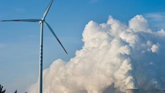 Eine Windturbine vor einem Kernkraftwerk (Symbolbild)